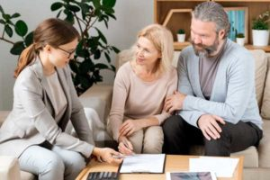 photo of a financial advisor speaking with a couple about HSA plan